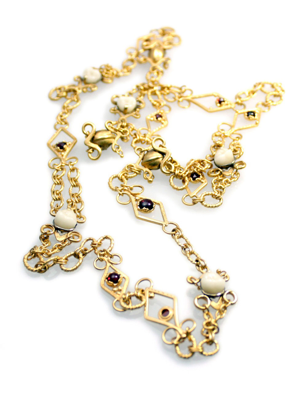 Anastasia Young. Necklace: Chain Dentata, 2011. 24 ct gold vermell on fine and sterling silver, porcelain crowns, garnets. 100 cm.